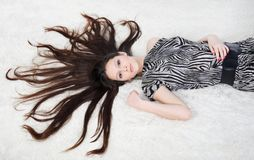 Beautiful girl with long hair lies on white fur Royalty Free Stock Photography