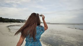 A beautiful girl with long hair in a long blue dress strolls along the beach. Girl posing on camera on exotic coast stock footage