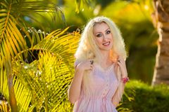 Beautiful girl with long hair and long legs. In rose dress in tropical vacation Royalty Free Stock Image
