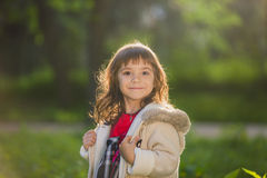 Beautiful girl with long hair in motion whirls and smiles, during sunset in the park. The concept of childhood and freedom. Stock Image