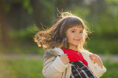 Beautiful girl with long hair in motion whirls and smiles, during sunset in the park. The concept of childhood and freedom. Royalty Free Stock Photo