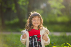Beautiful girl with long hair in motion whirls and smiles, during sunset in the park. The concept of childhood and freedom. Royalty Free Stock Image