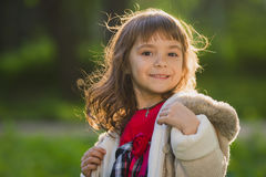 Beautiful girl with long hair in motion whirls and smiles, during sunset in the park. The concept of childhood and freedom. Royalty Free Stock Images