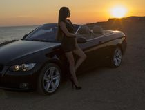 Beautiful girl with long hair posing beside a cabriolet on sunset Stock Photography