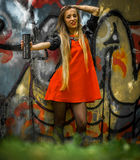 Beautiful girl with long hair in a red dress on  background of graffiti Royalty Free Stock Photo