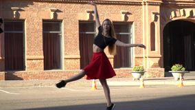 Beautiful girl with long hair in a red skirt dances in a city square on the outskirts of a building made of red brick stock video
