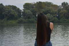 Beautiful girl with long hair at riverside. Beautiful girl with long hair at riverside relaxing in the autumn Stock Photo