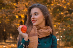 Beautiful girl with long hair and scarf looks away  holds an Apple in his hand, close-up Stock Image