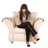 Beautiful girl with long hair sitting in armchair. Royalty Free Stock Photography