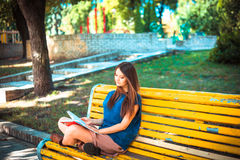 Beautiful girl with long hair sitting on bench in Stock Photos