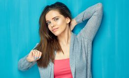 Beautiful girl with long hair standing against  blue wall back. Isolated studio portrait Royalty Free Stock Photos