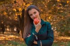 Beautiful girl with long hair stands in the Park and holds Apple near mouth Royalty Free Stock Images