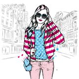 A beautiful girl with long hair in sunglasses, a jacket, a T-shirt and jeans. Fashion and style, clothing and accessories. Vector illustration Stock Images