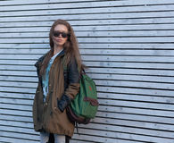 Beautiful Girl Long Hair. Tourist jacket, Sunglasses, Backpack. white wooden wall. Royalty Free Stock Image