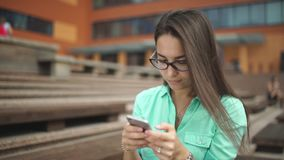Beautiful girl with long hair is typing a message on the phone stock video footage