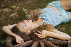 Beautiful girl with long hair  in the village. A girl lying on a wooden wheel in the garden Royalty Free Stock Image