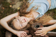 Beautiful girl with long hair  in the village. A girl lying on a wooden wheel in the garden Stock Photography