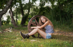 Beautiful girl with long hair  in the village. Summer day in the village. A girl sitting next to a wooden wheel Stock Photography
