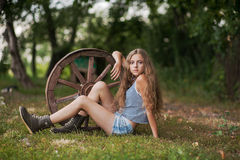 Beautiful girl with long hair  in the village. Summer day in the village. A girl sitting next to a wooden wheel Royalty Free Stock Photo