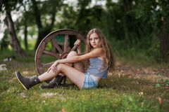 Beautiful girl with long hair  in the village. Summer day in the village. A girl sitting next to a wooden wheel Royalty Free Stock Photos