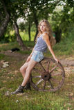 Beautiful girl with long hair  in the village. Summer day in the village. A girl sitting on a wooden wheel Stock Photography