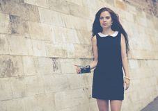 Beautiful girl with long hair with a vintage camera on an old European street. Colorful hipster photo Royalty Free Stock Photography