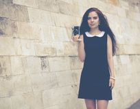 Beautiful girl with long hair with a vintage camera on an old European street. Colorful hipster photo Stock Images