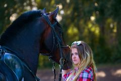 Beautiful girl with long hair on a walk with a horse. Royalty Free Stock Photo