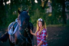 Beautiful girl with long hair on a walk with a horse. Stock Photos