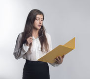 Beautiful girl with long hair wearing glasses. Young woman holding a yellow folder with documents and eyeglasses Royalty Free Stock Photos