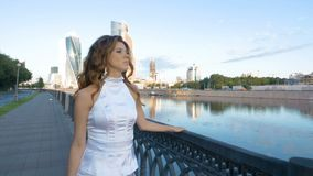A beautiful girl with long hair in white clothes is walking along the city embankment. stock video