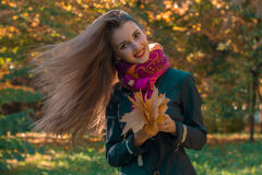 Beautiful girl with long hair who fly on the wind keeps the leaves in their hands and smiles Stock Photo