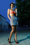 Beautiful girl with long legs and heels. Beautiful girl in orange bra and short skirt at night in park Royalty Free Stock Photos