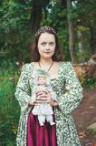 Beautiful girl in long medieval dress with vintage doll royalty free stock photos