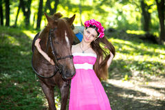 Beautiful girl in long pink dress near big brown horse. Spring, forest, sunny day, beautiful woman with wreath of flowers, shiny smile, standing near big brown Stock Photo