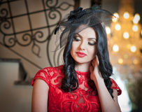 The beautiful girl in a long red dress posing in a vintage scene. Stock Photo