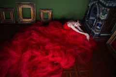 Beautiful girl in long red dress and in royal crown Royalty Free Stock Images