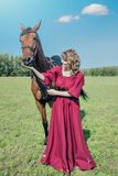 Feeds the horse from the hand. Beautiful girl in a long red dress stands next to the brown horse and Feeds the horse from the hand stock images