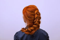 Beautiful girl with long red hair, braided with a French braid, in a beauty salon. Professional hair care and creating hairstyles stock photography