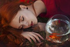 A beautiful girl with long red hair in the rays of light sleeps next to a goldfish in an aquarium. Young redheaded woman