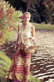 Beautiful girl in a long skirt. With a basket of grapes outdoors shooting Royalty Free Stock Photo