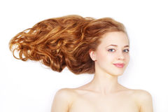 Beautiful girl with long wavy hair. On light background Royalty Free Stock Photo