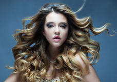 Beautiful girl with long wavy hair. Blonde with curly hairstyle and pink  lips. Close up Stock Images