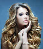 Beautiful girl with long wavy hair. Blonde with curly hairstyle and pink  lips. Royalty Free Stock Photography