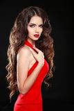 Beautiful girl with long wavy hair in red dress. Brunette with c. Urly hairstyle posing isolaled on black background Stock Photos