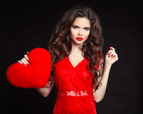 Beautiful girl with long wavy hair in red dress holding valentin Stock Photos