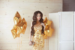 Beautiful girl with long wavy shiny hair. Brunette woman with elegant hairstyle in golden dress over party star balloons. Party royalty free stock photos