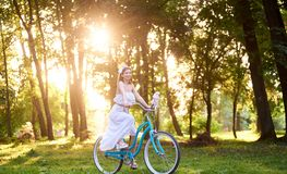 Beautiful girl in white dress holding peonies while riding blue bike down beautiful sunny park alley royalty free stock image