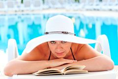 Beautiful girl look in a white hat on a sun lounger beside the pool Stock Photo