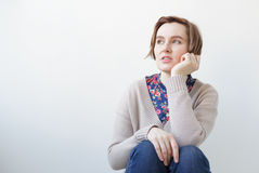 Beautiful girl looking aside. Beautiful girl in jeans and sweater sits at a white wall Royalty Free Stock Image